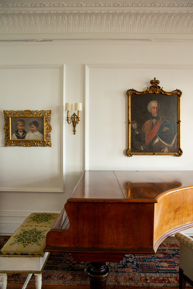 A grand piano sits against a wall decorated by two paintings in Porthpean House.  Wanderlost Magazine | Sam MacDonald