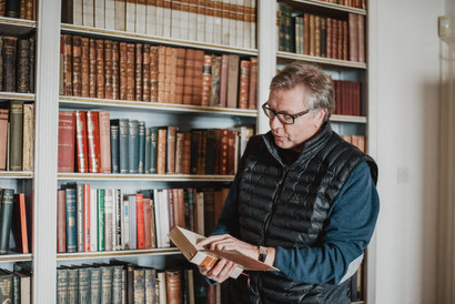 Martin Petherick, owner of the Porthpean beach house, reads a note written by his father in one of the books housed within the home's library.  Wanderlost Magazine   Mary Kathryn Carpenter