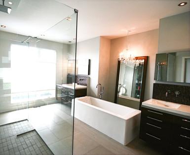 Cette salle de bain est tout en contraste avec les autres pièces de la maison. On y mélange des éléments classiques et chics, avec son chandelier de cristal et les lignes contemporaines du mobilier et de la baignoire. L'effet surprenant du mélange des style est réussi!
