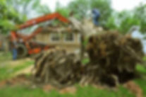 Large uprooted tree fallen over onto a house with two tree service workers and a red bulldozer