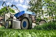 Close up of a blue lawnmower cutting grass