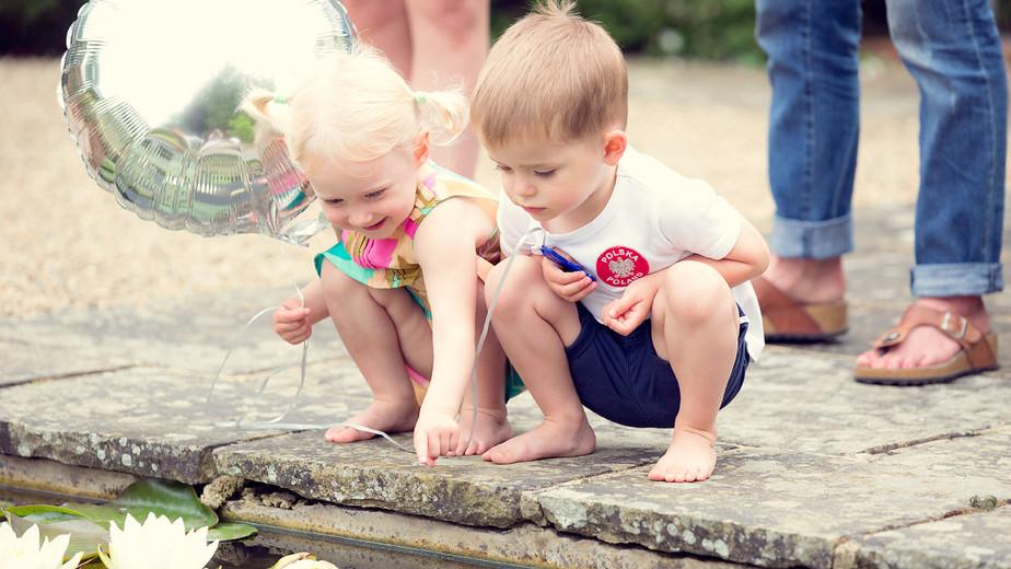 Children watching fish in a pond