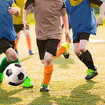 kids-playing-soccer-game-tournament-foot