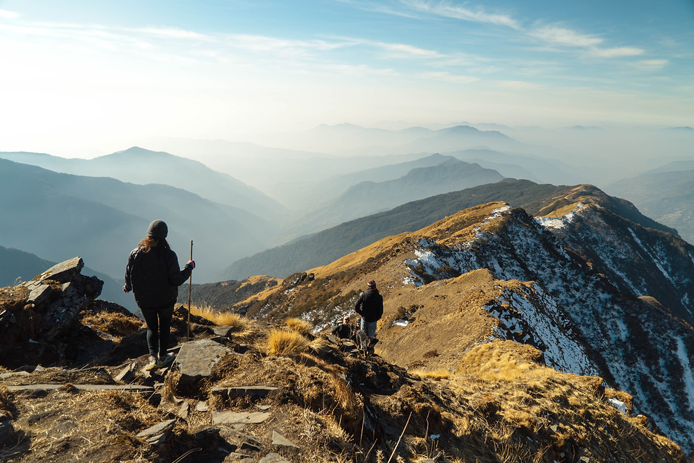 Two hikers on mountain ridge line.