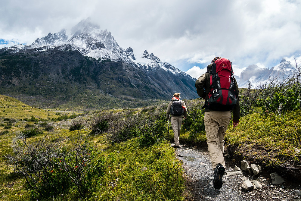 Two hikers in front of cloudy mountain.