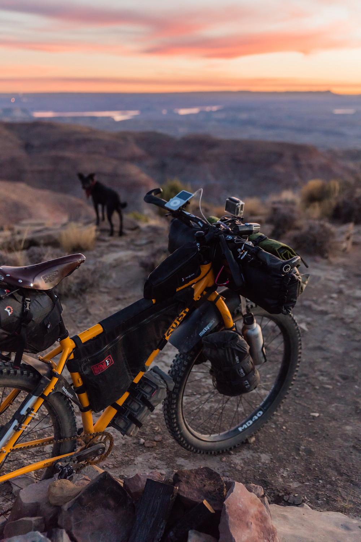 Bicycle atop rock at sunset.