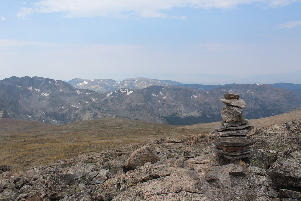 Tall rock cairn on top of mountain.