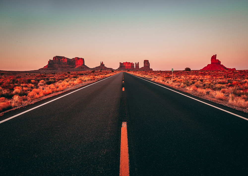 Tarmac road in desert at sunset