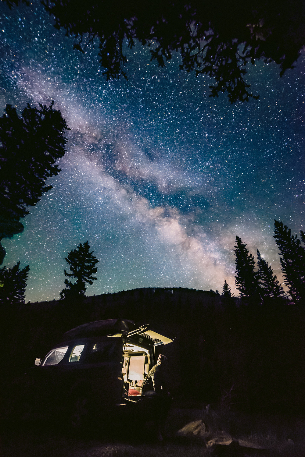 Milky Way above lit up car camping.