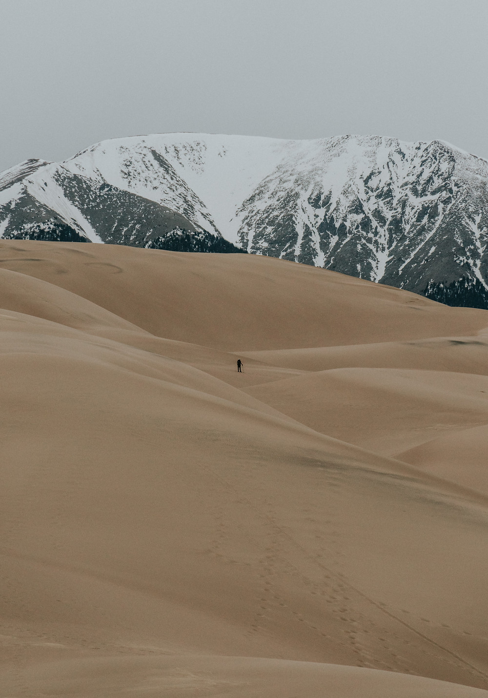 Person walks alone in the sand dunes of Colorado