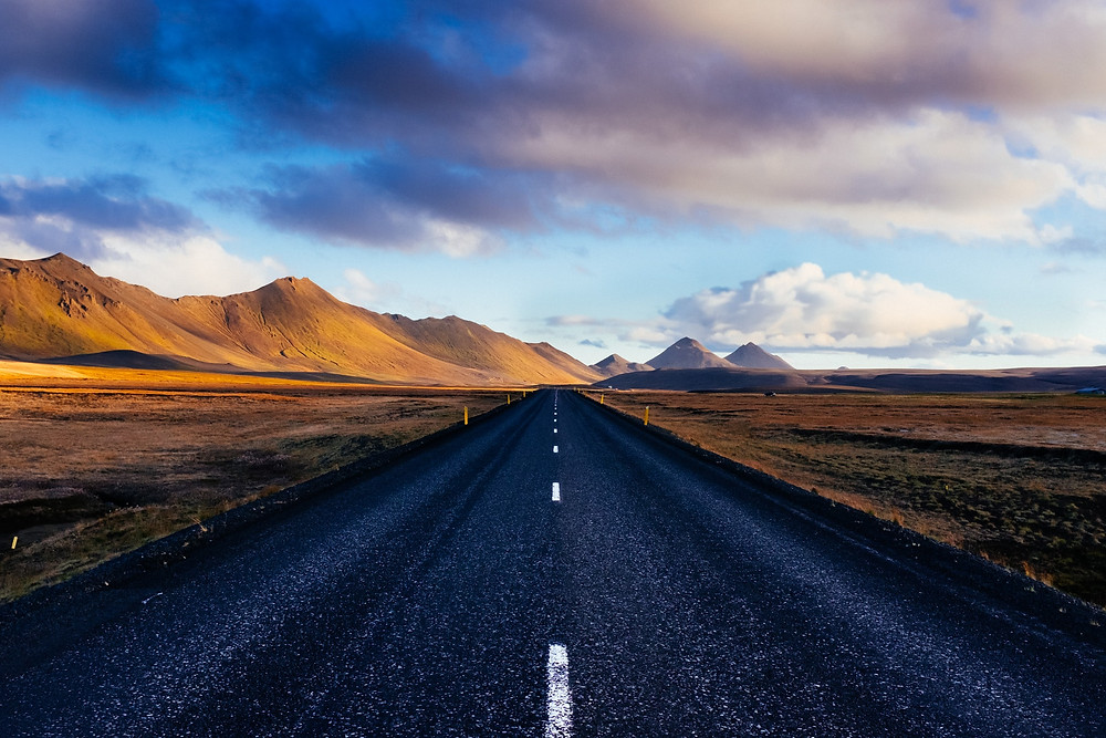 Open tarmac road through golden hills in Iceland.