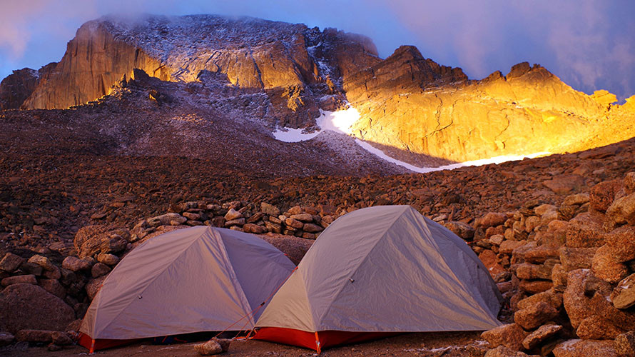 Two tents below mountain at sunrise