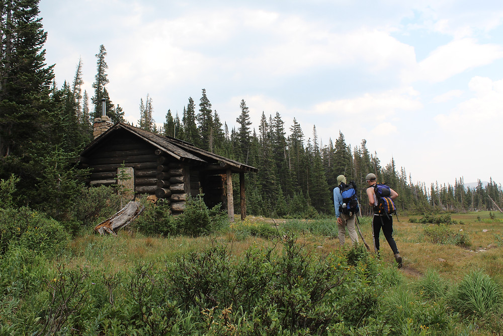 Two hikers by old log cabin in the forest.