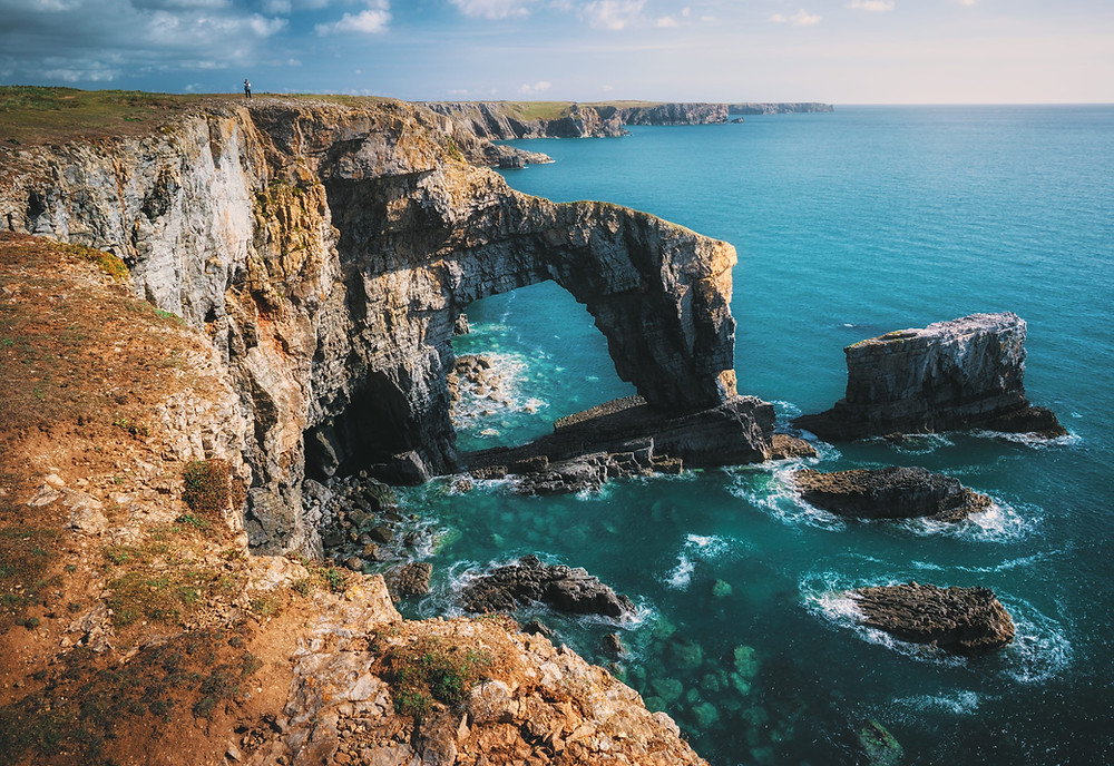 Red, rocky coast along a turquoise sea.