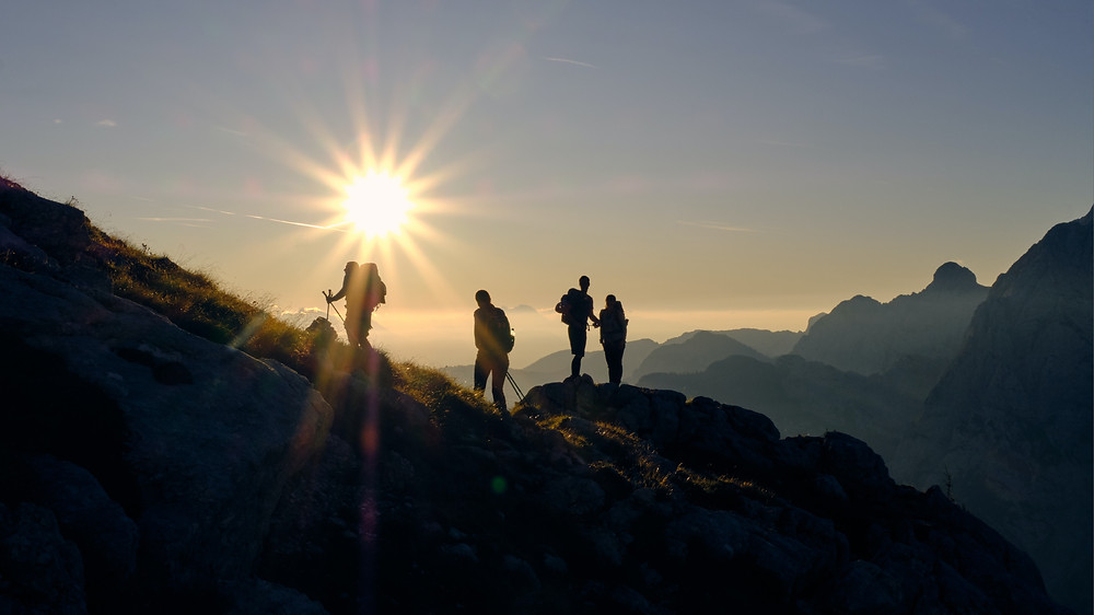 4 hikers on mountain in the sun.