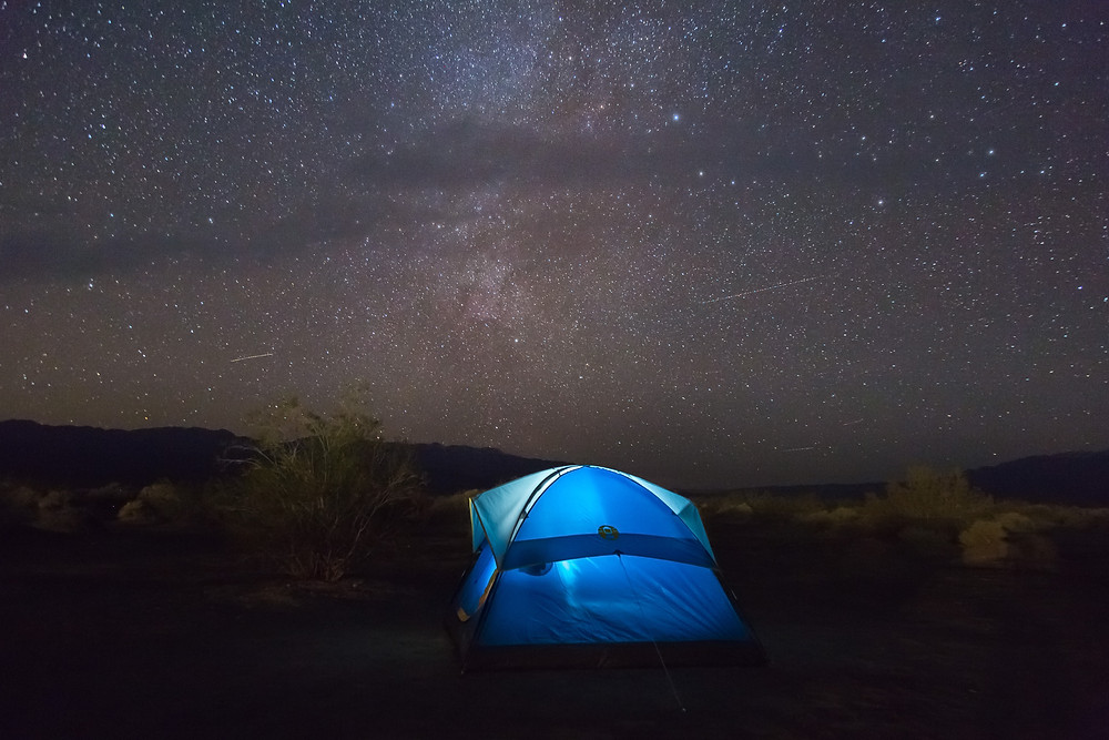 Blue tent in front of bright starry sky