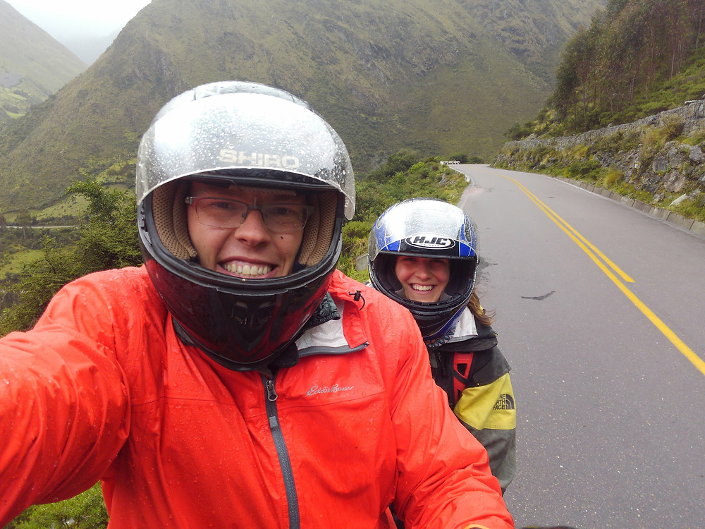 Two people in rain on motorcycle.