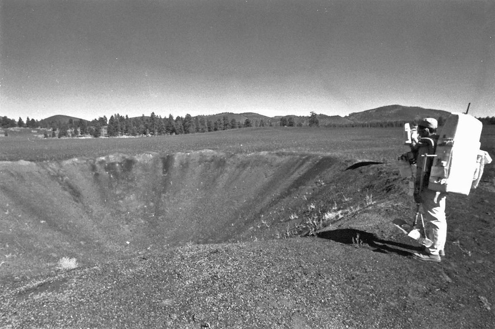 Astronaut in front of crater field.