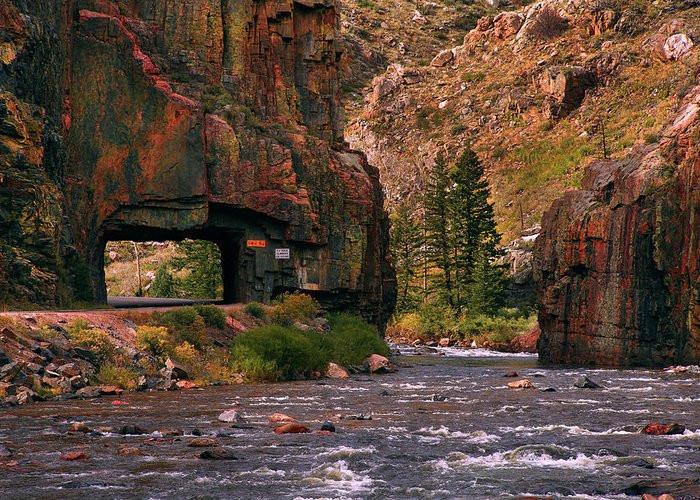 Road cuts through rock along river