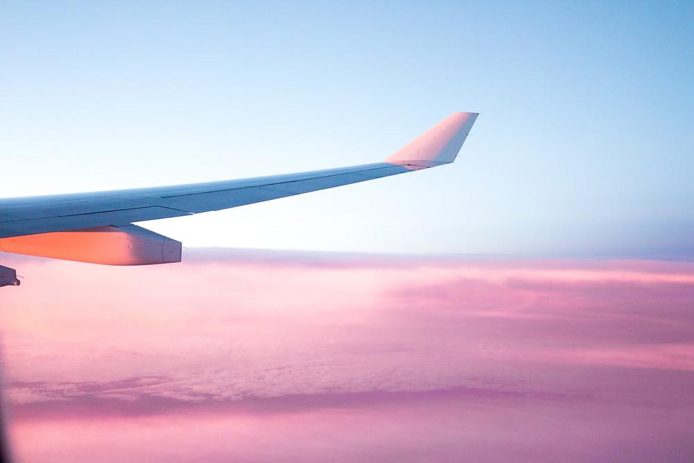 Plane wing during pink sunset.
