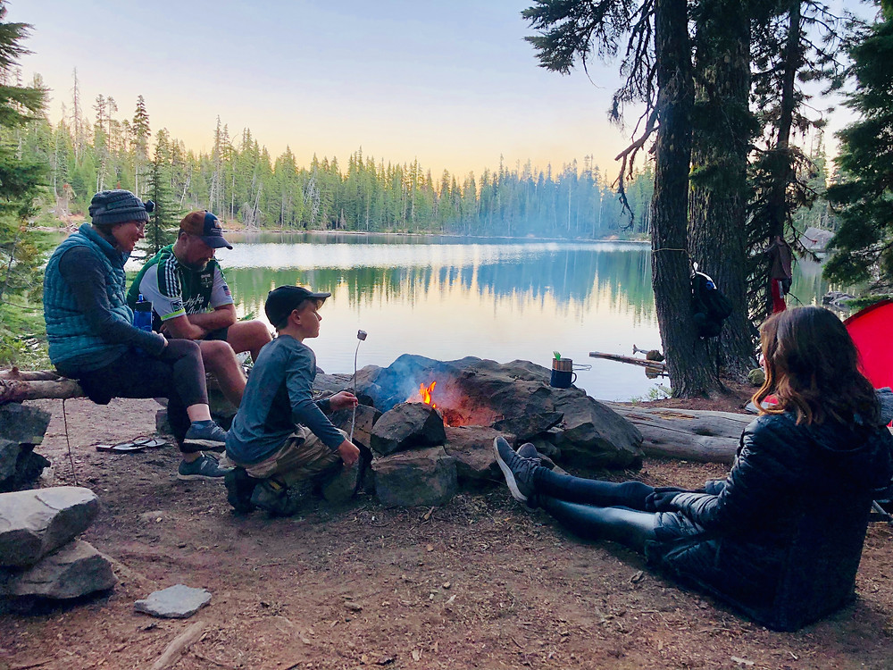 Family with a campfire along a mountain lake.
