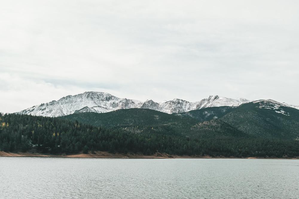 Snow peaked mountains behind lake.