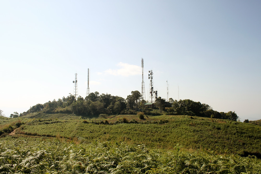 Cellphone towers on top of a green hill.