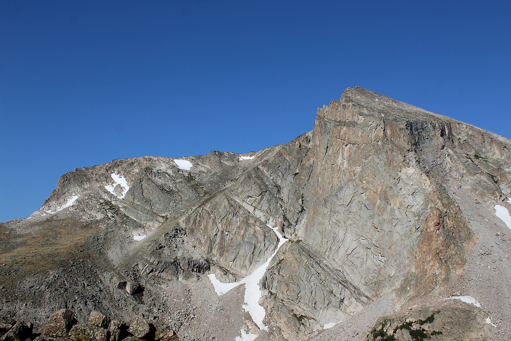 Tall, granite mountain face in front of blue sky.