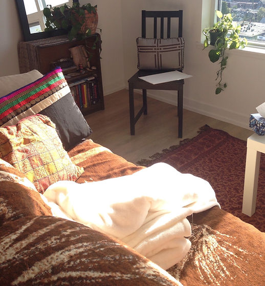 Picture of therapy office space with couch, chair, bookshelf and plants all bathed in sunligt