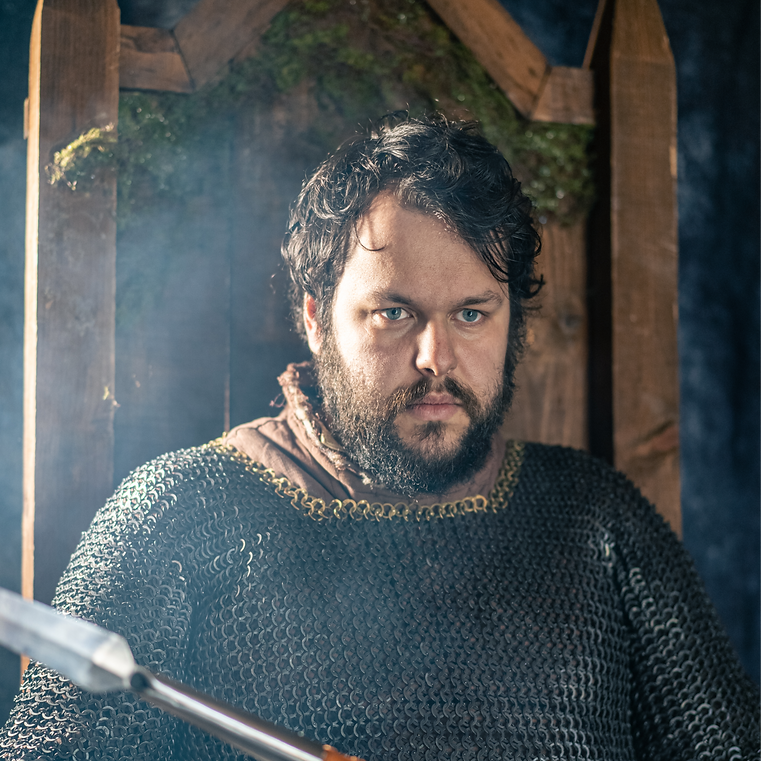 A man in chain mail sitting on a throne with a spear.