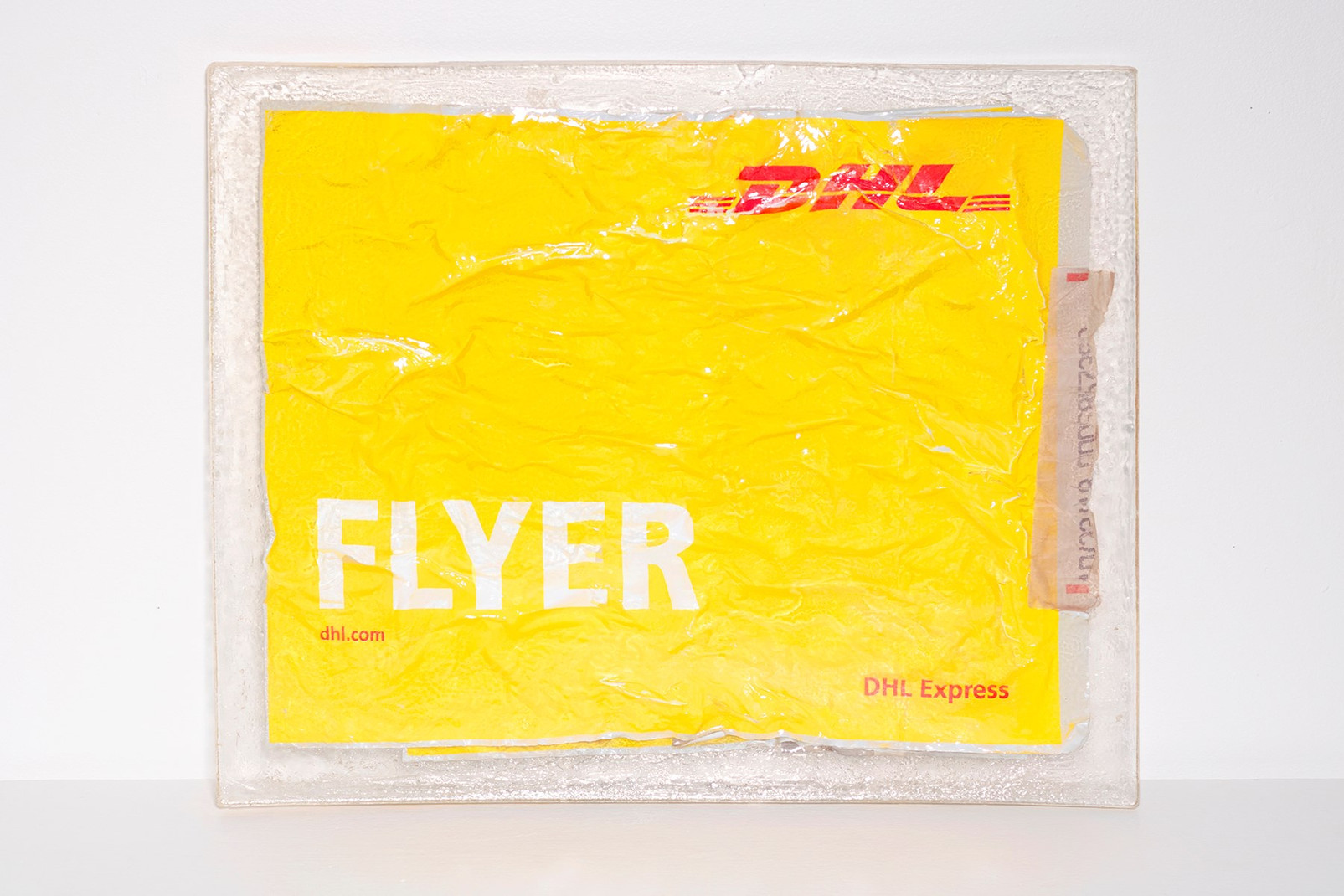 """Dalila Sanabria, """"Visas,"""" 2019. Resin slab of DHL flyers, unframed, 17 x 21.75 x 0.5 in. Image courtesy of the artist"""