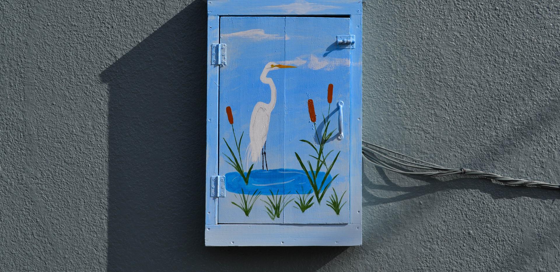 Egret on small telephone box