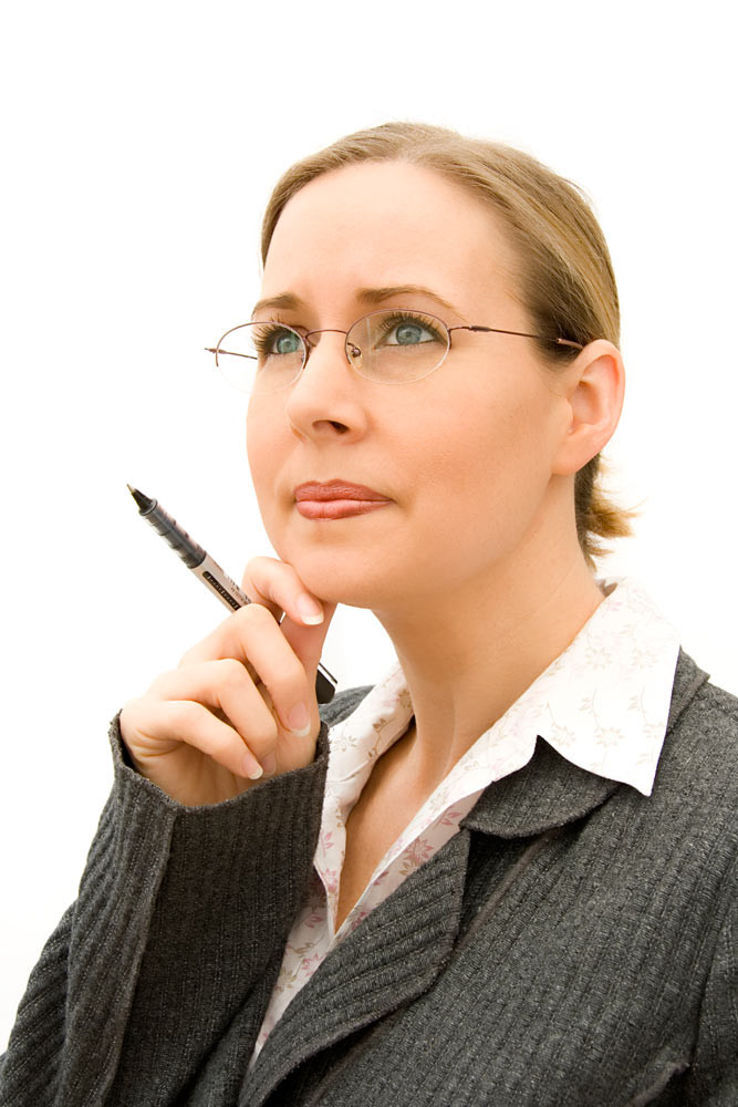 Woman in suit holding a pen and touching her chin