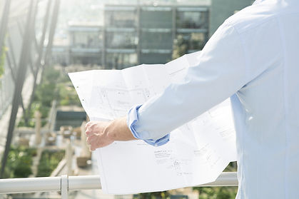 A boy with a white shirt looks at a project on paper.