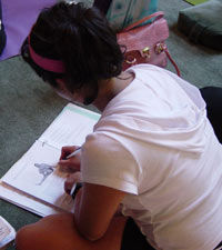 student studying the yoga teacher training manual at the Amrit Yoga Institute