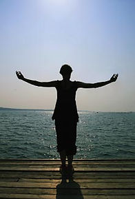 woman standing with open arms at Lake Kerr at the Amrit Yoga Institute