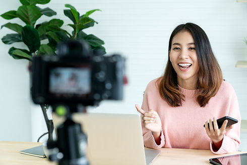 Confident young asian woman presenting on camera