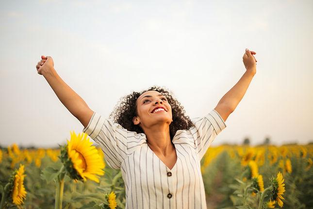 beautiful confident woman in field of sunflowers feeling free