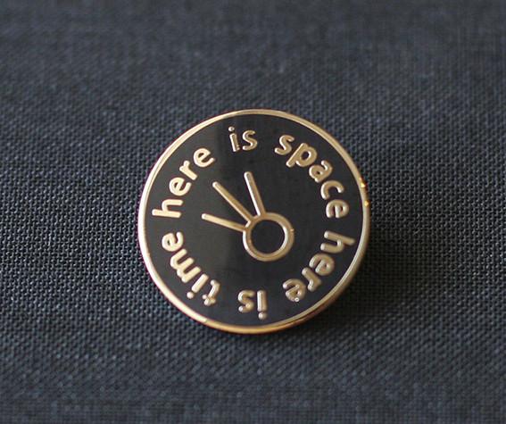 Here is space here is time, enamel badge