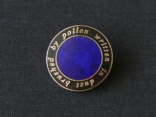 Brushed by pollen written in dust, enamel badge