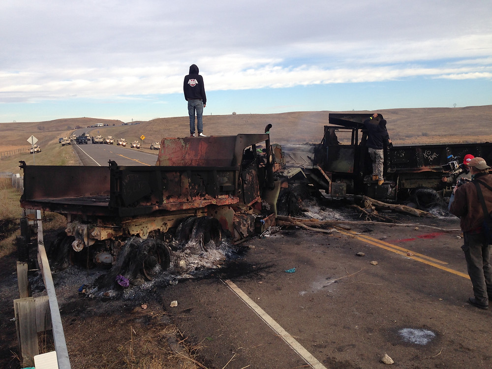 Morton County trucks wedged onto bridge by Morton County Sheriffs, armored cars in background