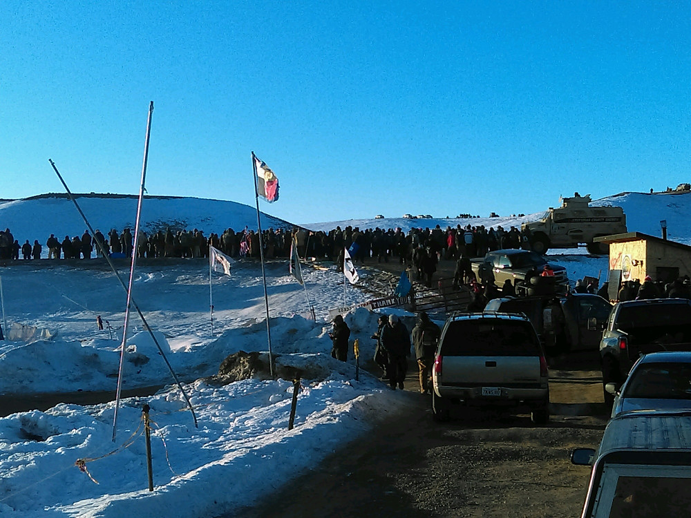 Looking up hill to main gate to Oceti Sakowin, Sherrifs on ridge top and road, Photo: Riley Redhorse