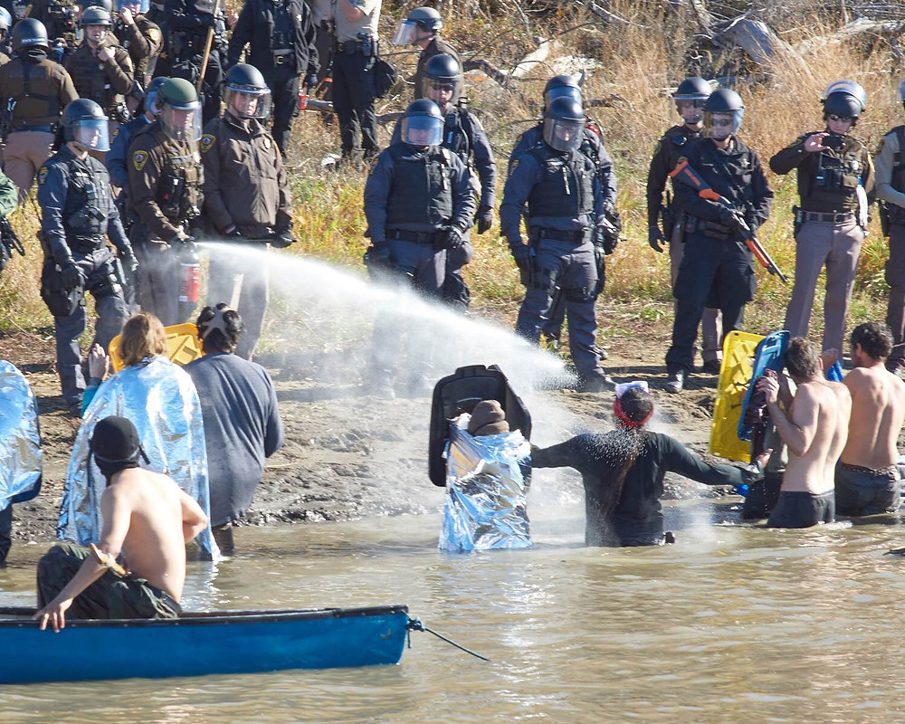 Police gas motionless water protectors at Turtle Island, photo Alonzo Macias