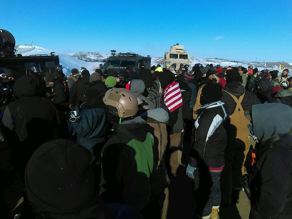 Water Protectors face off against Sheriffs and police below new camp at Standing Rock. Photo: Riley Redhorse