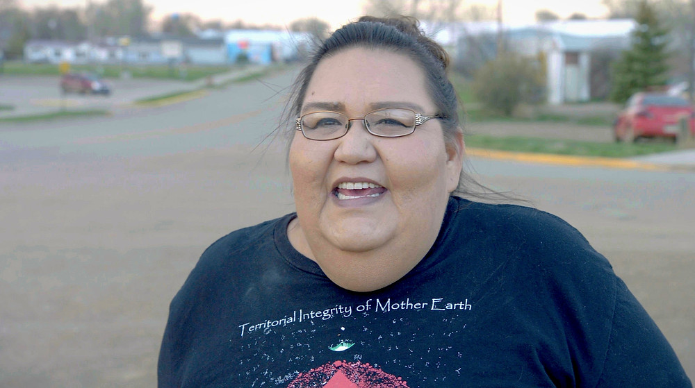 Joye, Braun, Indigenous Environmental Network, Community Organizer stands at the end of the main commercial street of Eagle Bute, SD, Cheyenne River Sioux Reservation