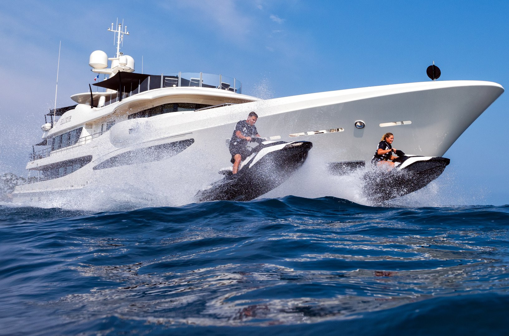 Super yacht ELIXIR - charter guests jumping on jetskis around the yacht