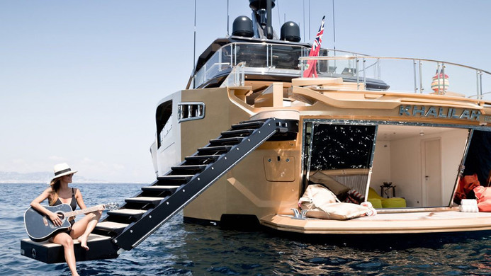 The ultimate mega yacht charter beach club - playing guitar over the sea!