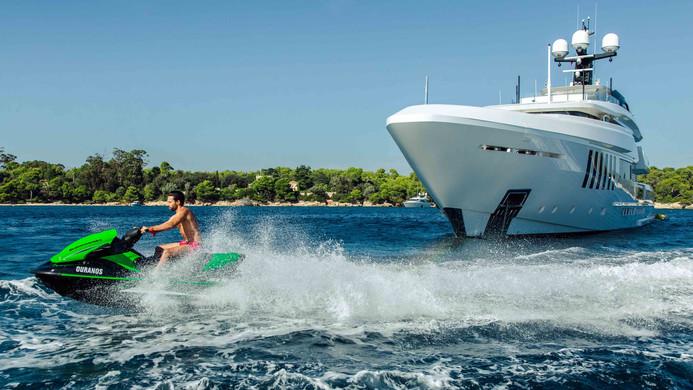 Mega yacht at anchor with jet ski