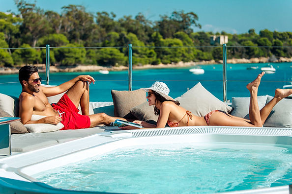 Couple enjoying a mega yacht charter, chlling by the hot tub on the sun deck.