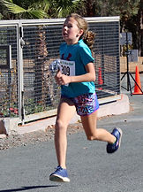 Anna Cobb, age 10 crossing the finish line as first WOMAN on the challenging 5k wth a 6:55 pace.